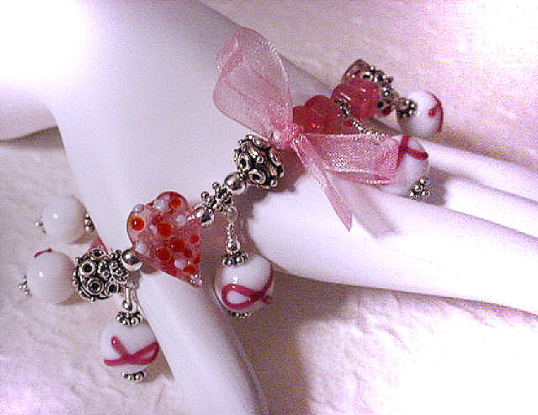 Cancer Awareness Bracelet - Handcrafted with glass beads and bali sterling silver. Stretch cord for size flexibility. Pink organza ribbon. SS bali beads may vary in design, depending on availability. Just Exquisite