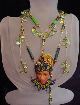Polymer Clay Jewelry Fairy Face Green Necklace-Handmade with Polymer Clay. Findings, crimps and clasp are 14K gold plated. Gold plated Beadalon .018 in wire is also used. Glass and brass beads are used for final details. Water pearl for final detail. Unique design!Beautiful and unique for that special occasion!