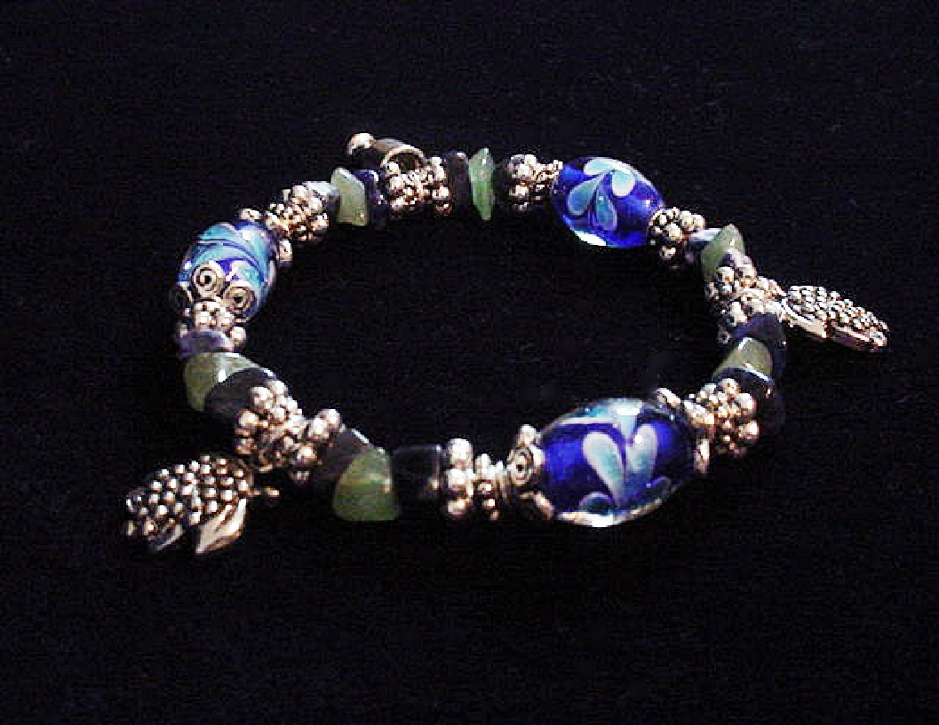 Handcrafted Jewelry Blue & Green Glass Beads Bracelet -Handcrafted with Blue Glass and Green Semi-precious stones beads. Transparent Lampwork White and Blue flower glass beads are used for a floral and romantic look. Embellished with Silver plated beads, charms and findings. Stretch cord is used for flexibility.Beautiful and Elegant!