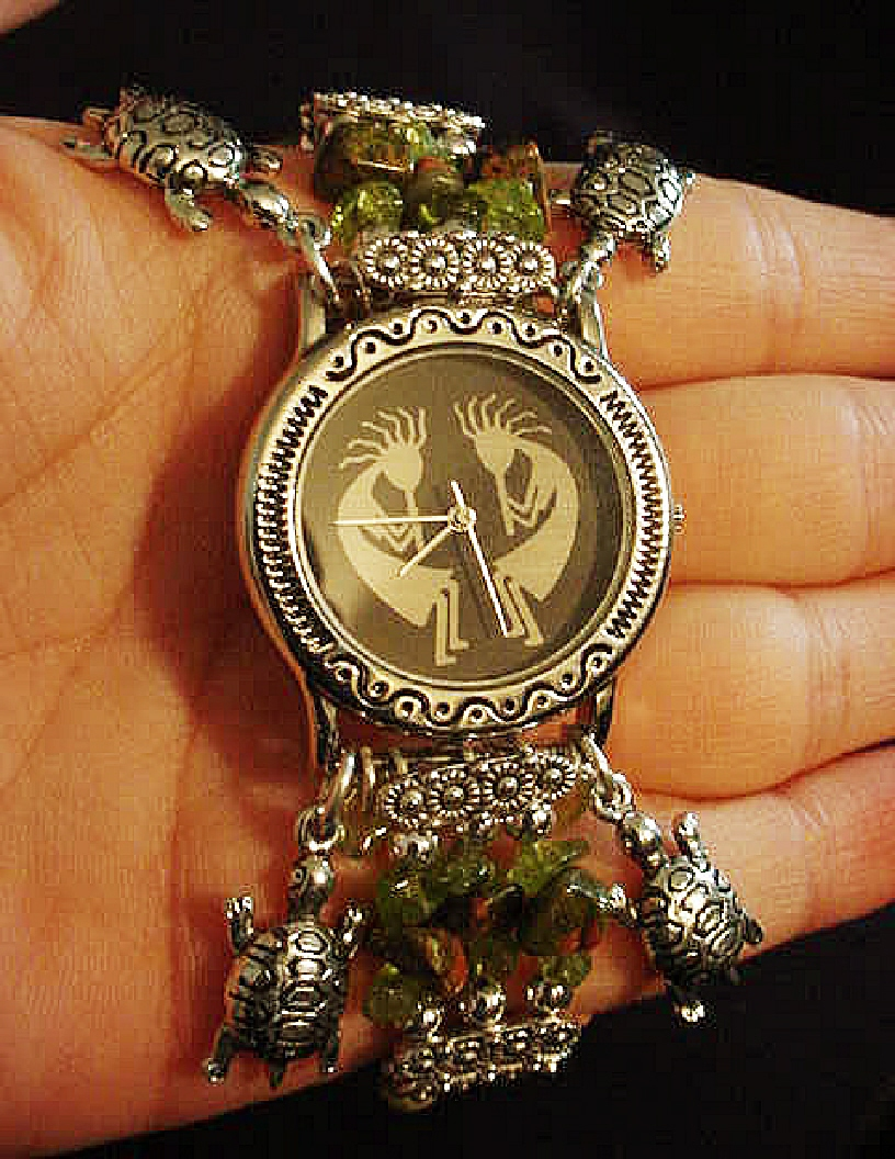Handcrafted Semi-precious Kokopelli Watch 1-Handcrafted with Semi-precious Unachite and Peridot Stones. Embellished with Silver plated beads and findings. Five turtle charms are used for final details. Stretch cord is used for watch bands. Round Large Silver watch face. Two Kokopelli's designs enhance the watch sphere. Quartz function and mechanical system. Stainless Steel back. Beautiful, Elegant and Southern look.