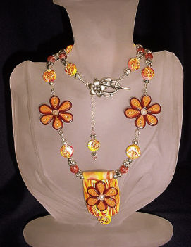 Orange and Yellow Flowery Necklace-Handmade Polymer Clay  Orange and Yellow beads. Handcrafted with Sterling Silver wire, crimps, chains and findings. Beadalon .018 in/19 stringing wire is also used. Embellished with fresh water pearls, crackle beads and Austrian crystals bicone beads for final details.Beautiful and unique for that special occasion.
