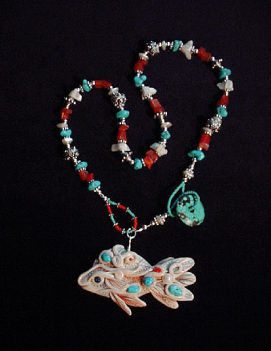 Handcrafted White Fish and Turquoise Necklace-Fish pendant handmade with polymer clay and embellished with Sleeping Beauty Turquoise Cabs. Fiber optic Orange and Mother of Pearls Beads are also used. Sterling Silver Bali Beads and findings. Turquoise medium doughnut is used as a clasp.Unique design!